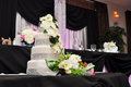 Pink uplighting in ball room wedding reception venue with fondant white floral cake Royalty Free Stock Photography