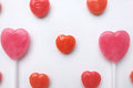 Pink Valentine`s day heart shape lollipop small red candy in cute pattern on empty white paper background. love concept. top view. Royalty Free Stock Photo