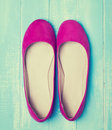 Pink woman shoes on blue colored wooden background Royalty Free Stock Photo