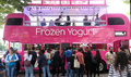 Pink yoghurt bus people buy frozen from a london which is transformed to a mobile vendor in south bank london Royalty Free Stock Photo