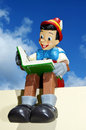 Pinocchio figure sitting on a wall reading a book this figure is part of a huge private collection of life size disney display Royalty Free Stock Photo