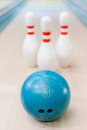 Pins and ball are great team close up of blue bowling lying against staying on bowling alley Royalty Free Stock Image