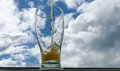 Pint of beer against blue sky dark brown pours in to the glass Stock Image