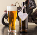 Pint of chilled golden beer in a glass with a good frothy head alongside the empty beer bottle with a heart on it either Royalty Free Stock Photos