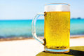 Pint of cold beer on top of the beach table close up a Royalty Free Stock Photo