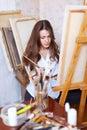 Pinturas de cabelos compridos do artista na lona Fotografia de Stock Royalty Free