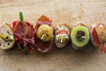 Pintxo Set: Olive, Anchovy, Cherry tomato, kiwi, Raisin, Cured Ham, Mushroom,  bread in a rustic board Royalty Free Stock Photo