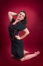 Pinup Girl in Black Dress Kneels Royalty Free Stock Photos