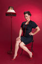 Pinup girl in black dress with lamp against red background Stock Photo