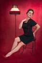 Pinup girl in black dress with lamp red textured background Stock Photo