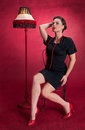 Pinup girl in black dress poses seductively red background Royalty Free Stock Photo