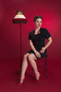 Pinup girl in black dress sits with fringed lamp against red background Stock Image