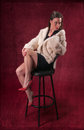 Pinup girl in black dress wearing fur coat on black stool red background with retro texture Stock Images