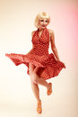 Pinup girl in blond wig retro dress dancing Royalty Free Stock Photo