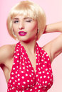 Pinup girl in blond wig and retro red dress winking. Vintage. Royalty Free Stock Photo
