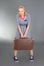 Pinup girl with brown retro suitcase over grey Royalty Free Stock Photo