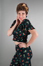 Pinup girl in flowered outfit cheeky grin on grey background Royalty Free Stock Image