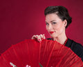 Pinup girl looks over red parasol background Stock Photos