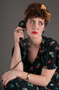Pinup girl looks upset by phone news grey background Stock Image