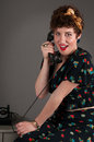 Pinup girl on old fashioned telephone grey background Stock Photo