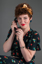 Pinup girl on old fashioned telephone smiles grey background Stock Photos