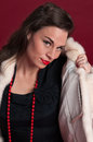 Pinup girl poses in white fur coat red background Royalty Free Stock Images