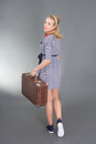 Pinup girl with retro suitcase over grey Royalty Free Stock Images