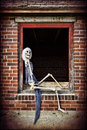 Pinup skeleton a female posing like a girl in the window of an old abandoned home Royalty Free Stock Photos
