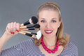 Pinup woman with make up brushes over grey Stock Images