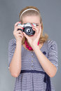 Pinup woman in retro clothes posing with photo camera over grey Stock Photos