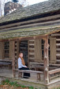 Pioneer woman a pregnant redhead sits on a rough wooden bench on the porch of her log cabin Stock Image