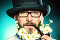 Pipe with flowers handsome smiling young man in glasses and a beard of Stock Images