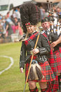 Pipe major marching at forres in full regalia with the band highland games on th july Royalty Free Stock Photo