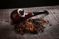 Pipe and tobacco on wooden surface Royalty Free Stock Photo