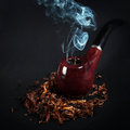 Pipe and tobacco on a wooden surface Royalty Free Stock Photo