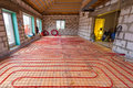 Pipefitter installing system of heating or underfloor heating installation. Water floor heating system interior.