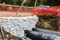 Pipeline passes under the road white sandbag bags are full with sand in wall formation to hold earth near traffic industrially Stock Photo