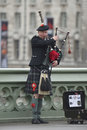 Piper at westminster bridge a dressed in traditional costume on london Royalty Free Stock Photo