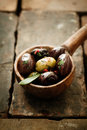 Piquant olives with a spicy chilli seasoning displayed in an old vintage wooden ladle or spoon on bricks with copyspace Stock Images