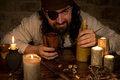 Pirate with rum and a lots of candles and goldnuggets, concept m Royalty Free Stock Photo
