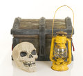 Pirate stuff a wooden treasure chest and skull beside a yellow oil lamp Stock Images
