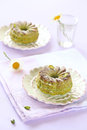 Pistachio cakes on white plates plate and kitchen towel a light purple background Royalty Free Stock Photography