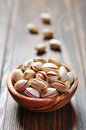 Pistachio nuts close up of a bowl of over wooden background Royalty Free Stock Photos