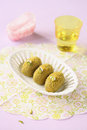Pistachio sweet balls in white vase for sweets with glass of water on light purple background Stock Photography