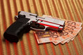 Pistol over euro bills Royalty Free Stock Photos