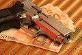 Pistol over euro bills Stock Photography
