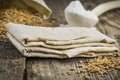 Pita bread with grains and flour on old wooden table Stock Photo