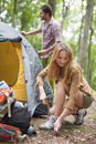 Pitch a tent couple unfolding in the forest Stock Photo