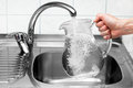 Pitcher being filled with drinking water from kitchen faucet.