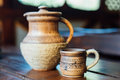 Pitcher and Cup of red clay with Ukrainian ornament on the wooden table Royalty Free Stock Photo